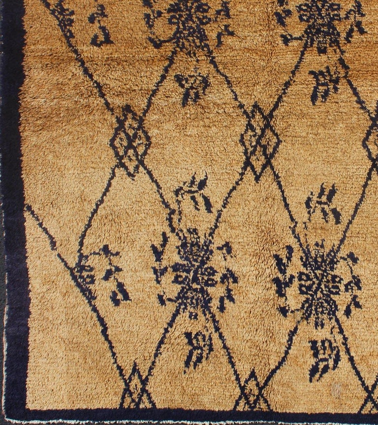 This unique Tulu demonstrates a balance between a tribal motif and a freely floating floral design. The navy pattern contrasts elegantly with the warm taupe background, encased by a solid, defined border. With its agrestic charm, plush pile and