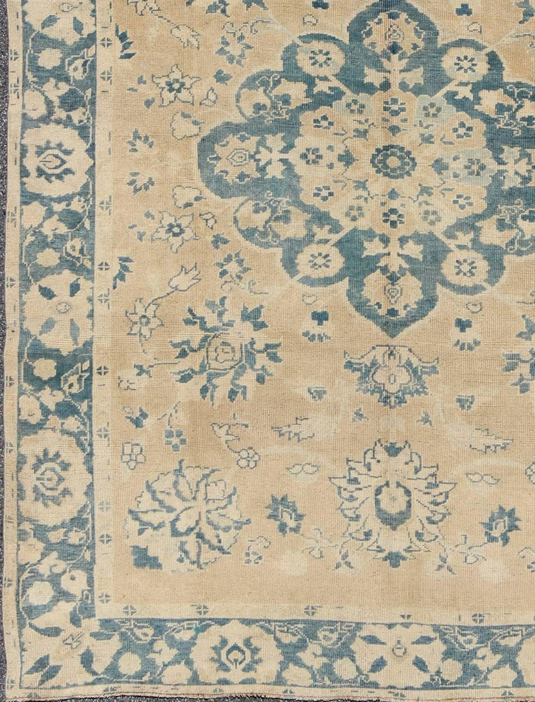 Handwoven in Turkey, this vintage Oushak rug features a large-scale medallion and floral bouquets. The butter yellow background is elegantly decorated by a variety of medium blue colors, which adds depth to this beautiful rug. Other colors include