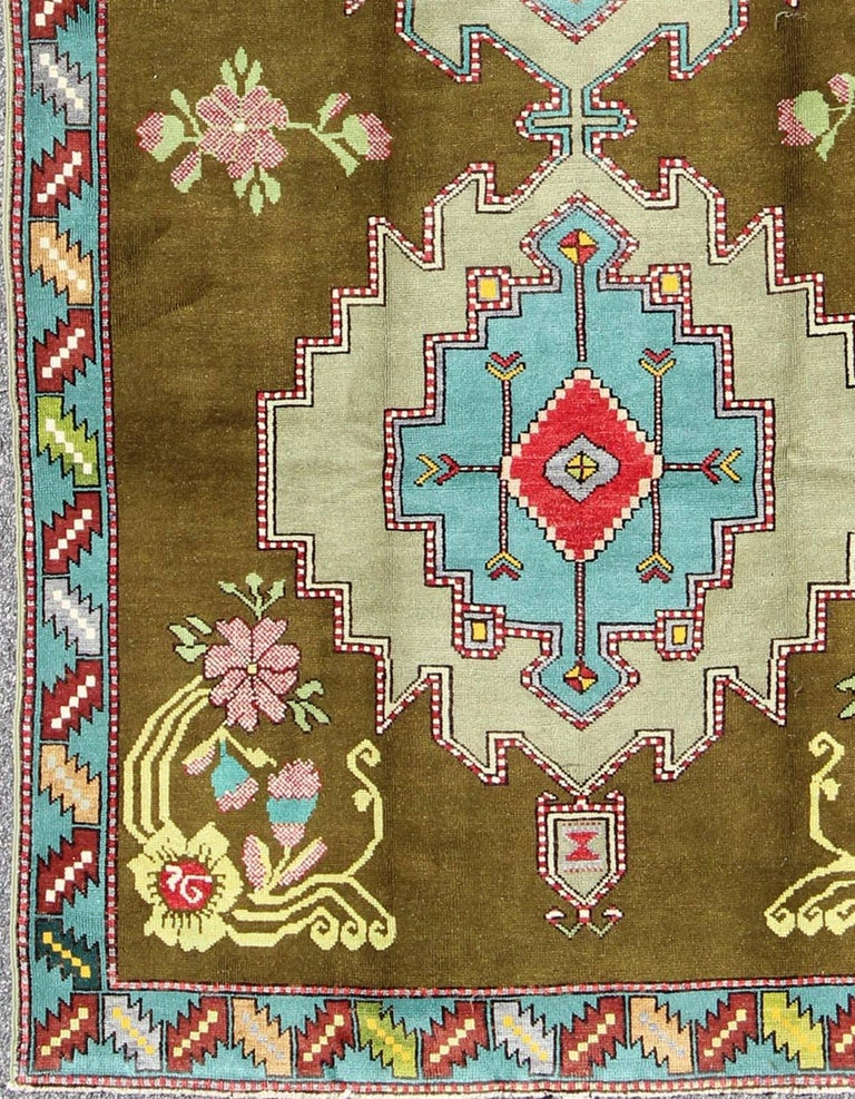 Unique Turkish Carpet in Green and Vivid Colors This lovely and unique Turkish carpet displays two geometric medallions in aqua, green, pink and red, which are boldly resting on a field of dark olive color. The four corners have vines and flowers
