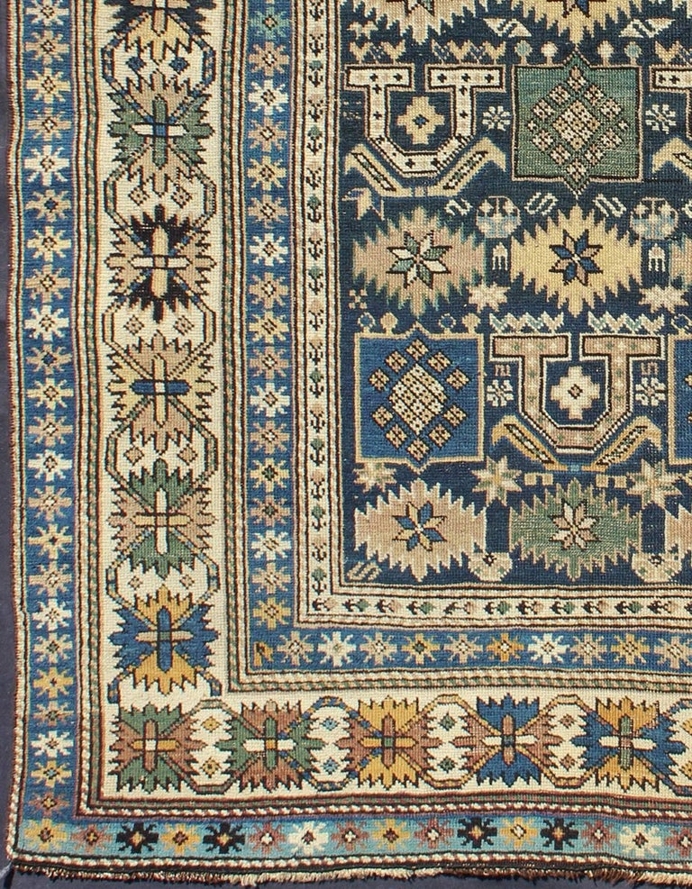 The field of this Caucasian piece features all-over tribal motifs and shapes decorated with small flowers and square designs, alternating colors between tan, blue, green and yellow. A blue background cradles the motifs with their squared edges and