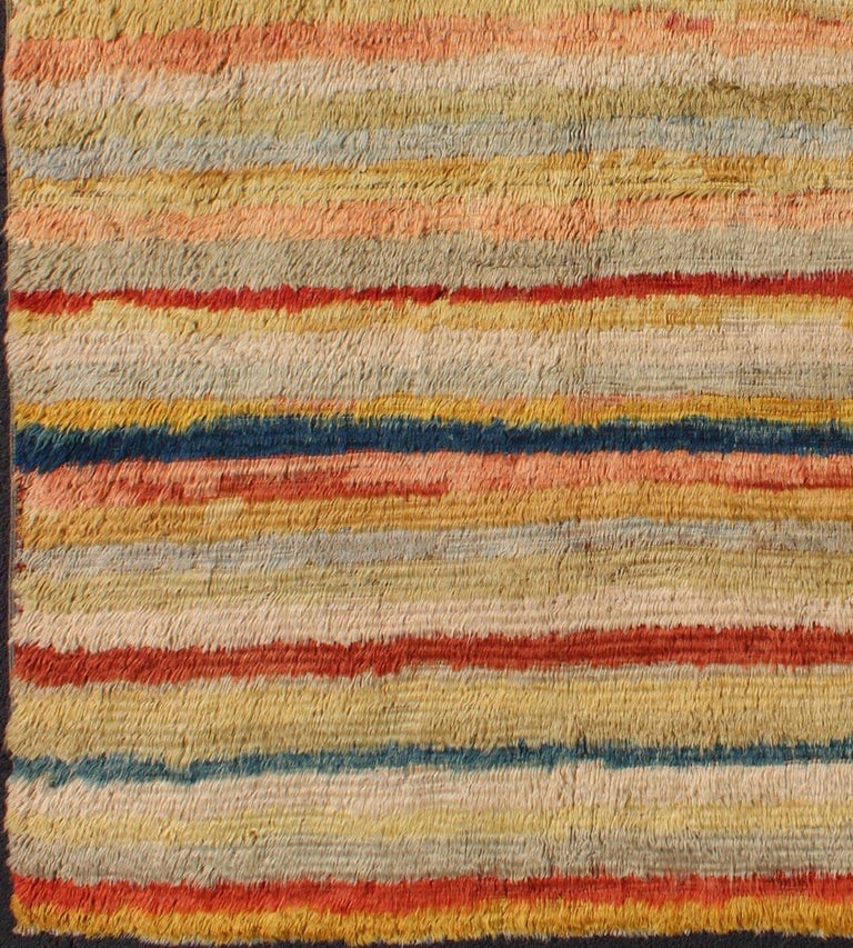 This high pile shaggy Tulu rug is handwoven from wool in a soft and colorful palette, featuring a striped pattern of both bold and muted tones. Tulu carpets' unique texture and unusual patterns transform interiors with a Bohemian aesthetic: