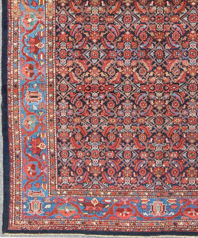 This magnificent antique Persian Malayer rug was hand-woven around the turn of the 19th century. It bears a stunning display of opulent colors and an all-over sub-geometric design. Colors include cobalt blue, berry blue, peacock blue, rust, light