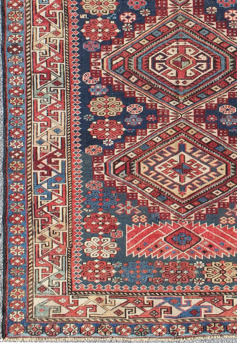 This antique, late 19th century Kazak rug from Russia displays three bold, geometric central medallions set on an indigo background and surrounded by multiple complementary geometric borders. Measures: 4'4 x 7'7. List Price: