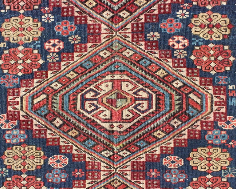 Wool Antique Kazak Rug with Geometric Medallions and Indigo Background For Sale