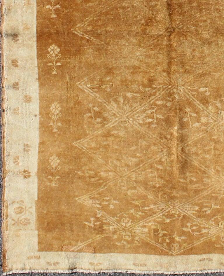 Light brown vintage Turkish Oushak rug with latticework floral pattern, rug tu-9501, country of origin / type: Turkey / Oushak, circa mid-20th century  Set on a light brown field with a latticework floral pattern, this beautiful vintage Oushak rug