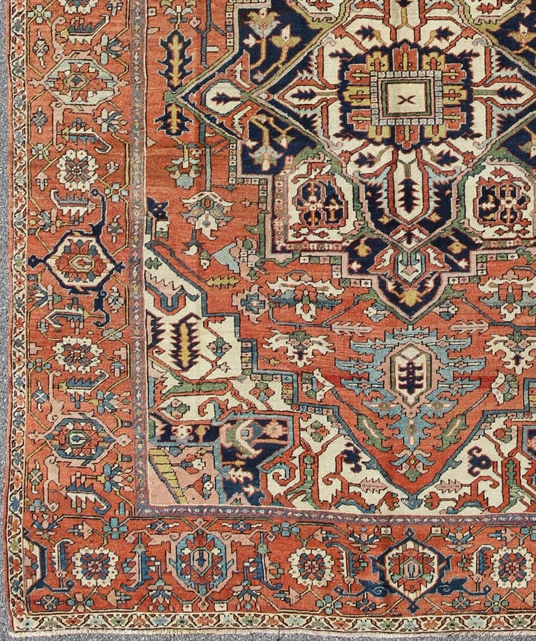 Antique Persian Serapi Rug with Bold Medallion in Orange, Navy Blue and Green. This magnificent antique Persian Serapi from the late 19th Century bears an exquisite design rendered in gorgeous, warm hues of rust, green, and denim blue. A highly