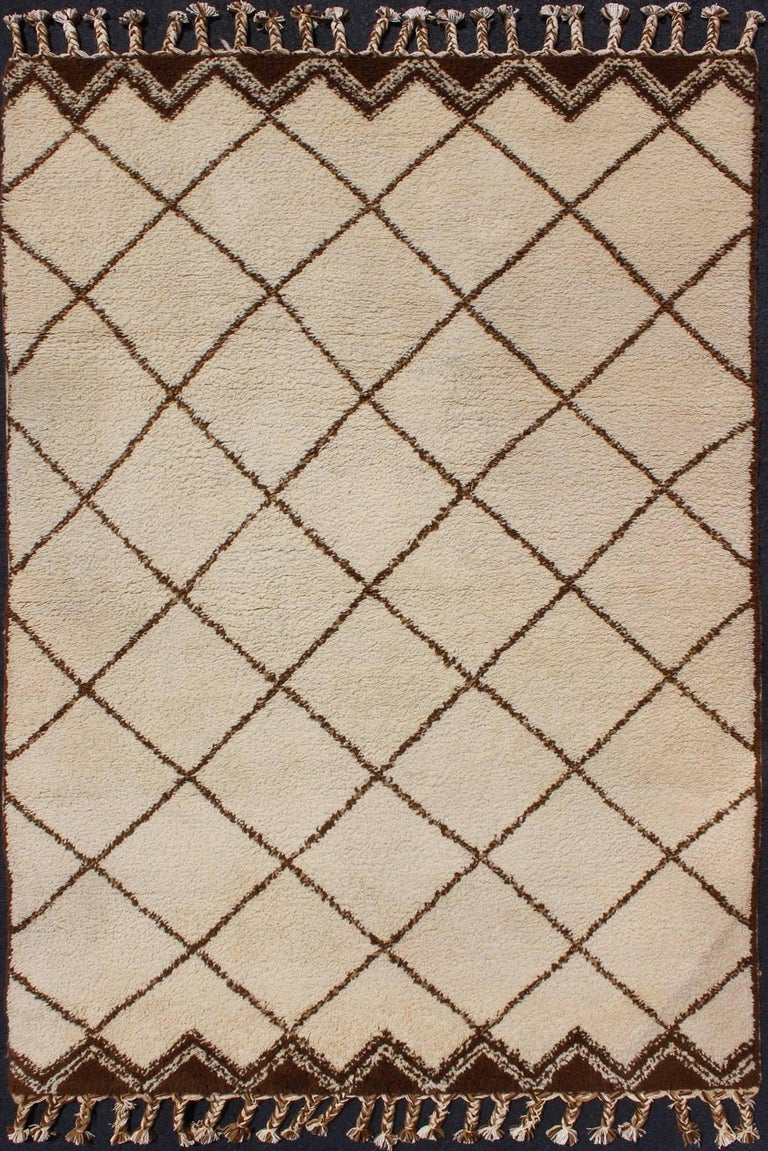This tribal, vintage 1950s Moroccan rug with diamond shapes features ivory and brown colors and fringed ends.