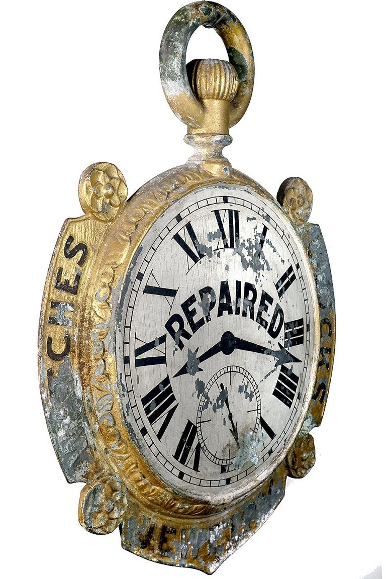 This impressive 19th century antique American outdoor storefront hanging jeweler or watchmaker trade sign is attributed to the Miller Co., Bellefontaine, OH. Visually striking and double-sided the pocket watch advertising sign features an ornamental