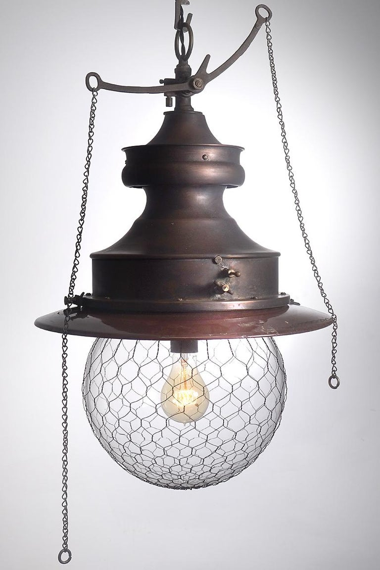 This is a unique copper bodied lamp with nice detail. I love the long are rocker gas valve with chains and the 12 inch diameter wire cage globe. This is the type of fixture that was often used in turn-of-century a general stores.