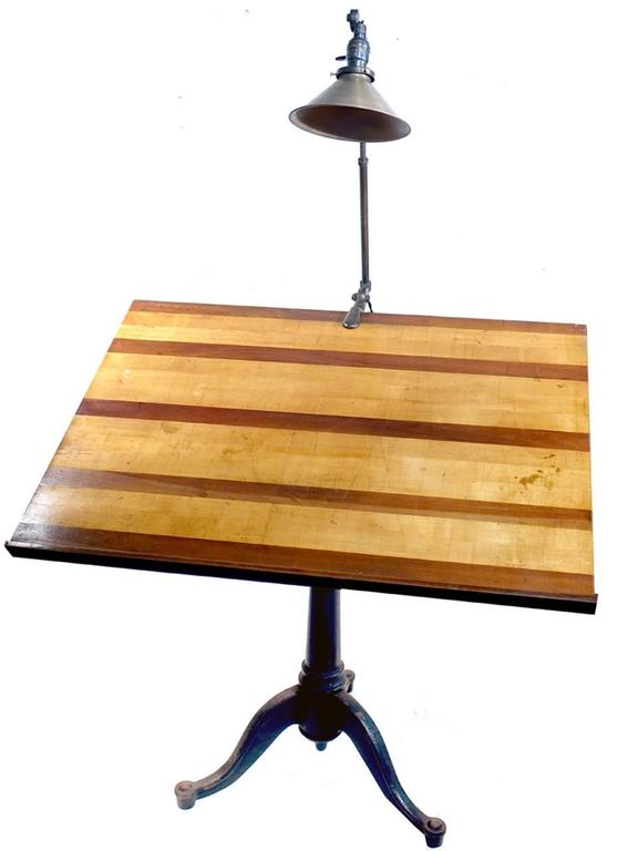 This is the quintessential architects drawing table. An articulating cast iron base and a beautiful contrasting wood drawing board. The table turns, moves up and down and tilts. In addition it comes with a beautiful and very sought after all brass