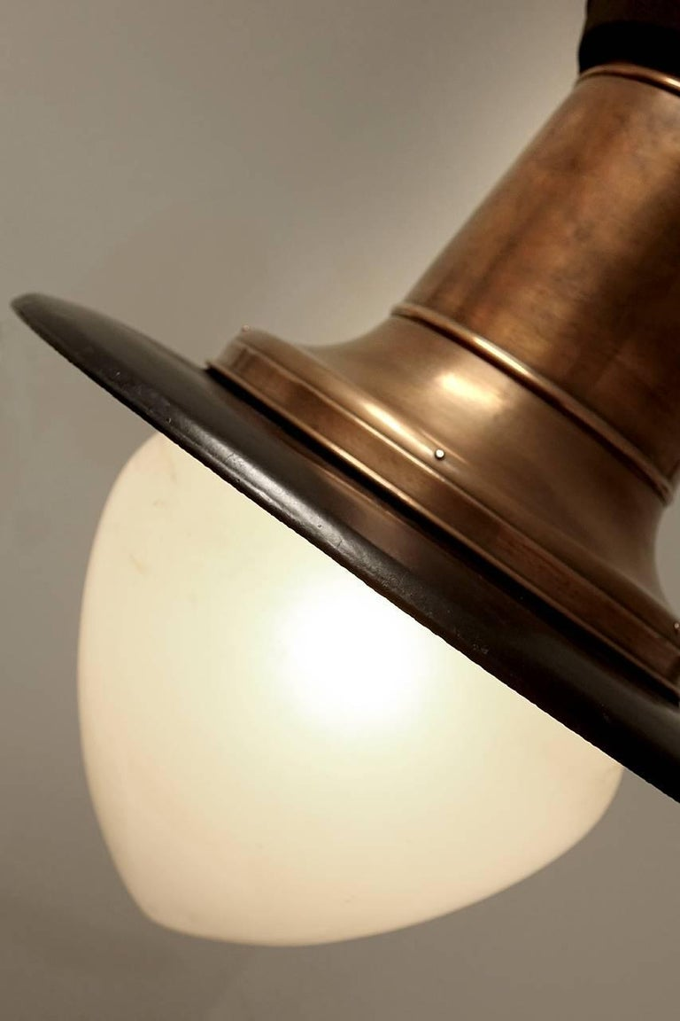 The finish of the bright copper and black porcelain have just the right look. In addition the original acorn milk glass dome make this impressive lamp a real standout. It has a 20 inch diameter shade and stands 28 inches tall. I believe these were