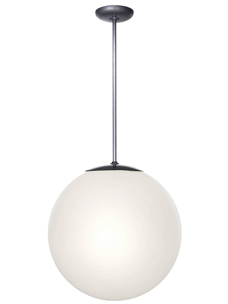 These late 1950s full moon milk glass globe lamps were a favorite of architects and designers of the period. They have a simple, clean and elegant design that have made them a Mid-Century Modern icon. We have a nice collection of these fixtures in