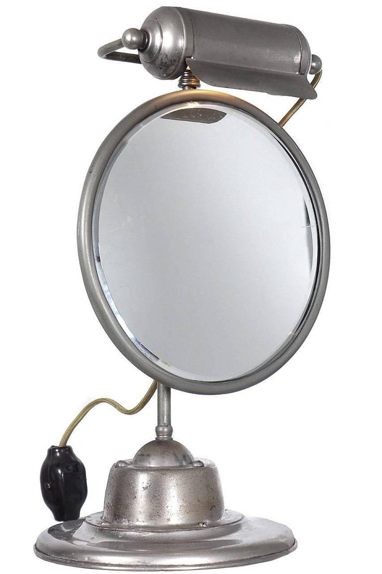 This is a nicely detailed make-up or shaving mirror. It looks to be all business with no decorative elements but lots of character. The base has an oversized articulating ball and the light is a horizontal shade not unlike an art lamp. It is mostly