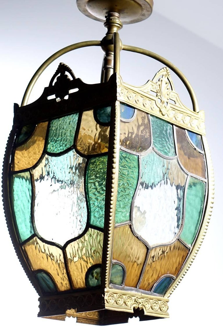 This Tudor style lamp is perfect for a front entrance, stair or hall. The medallion centered curved glass looks beautiful with or without light. Its all framed in detailed stamped brass.