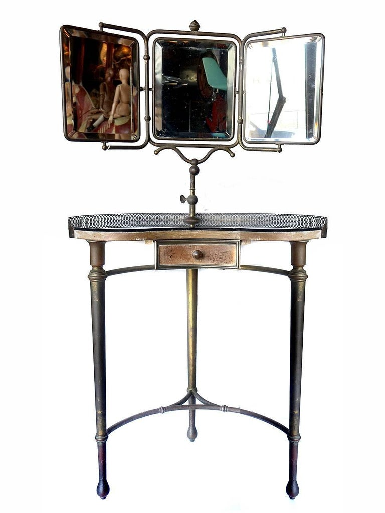 This early original table has a black glass top a d three beveled mirrors. The mirror frames and legs are brass having and dark aged patina. The table and draw are wood. I think the tables edge may have had a fabric fringe tacked on the front edge.