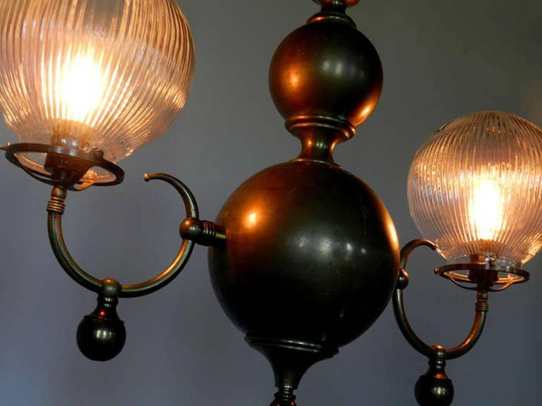 This lamp is a bit more traditional in style than what I normally offer. The repetitive spheres and holophane globes make this impressive double chandelier unique... I couldn't resist. Each prismatic globe is 8 inches and the total width is 28