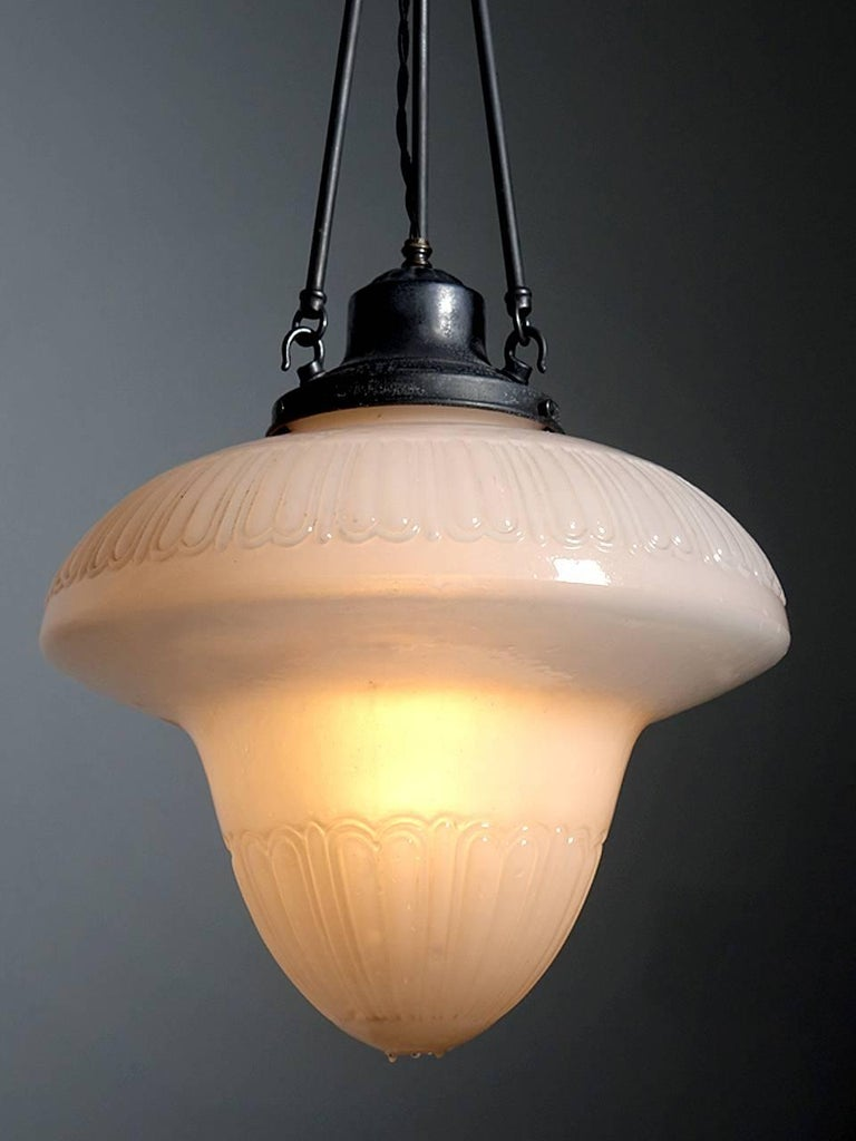 This is a large showy early 20th century milk glass fixture. It was a classic style often found lighting fancy stores and Pharmacies of that era. The ornate shade has an impressive 16 inch diameter and through a nice even light. The glass is a nice