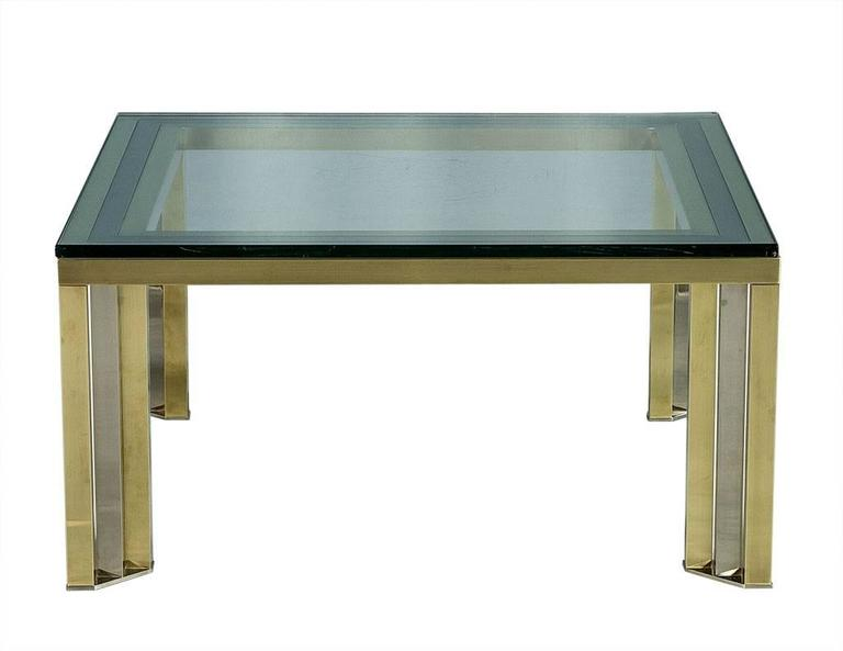 This Mid-Century Modern cocktail table is both elegant and futuristic. The design is attributed to Romeo Rega and it is comprised of polished brass and chrome legs top with a thick slab of glass. This piece is sharp enough to truly make a statement