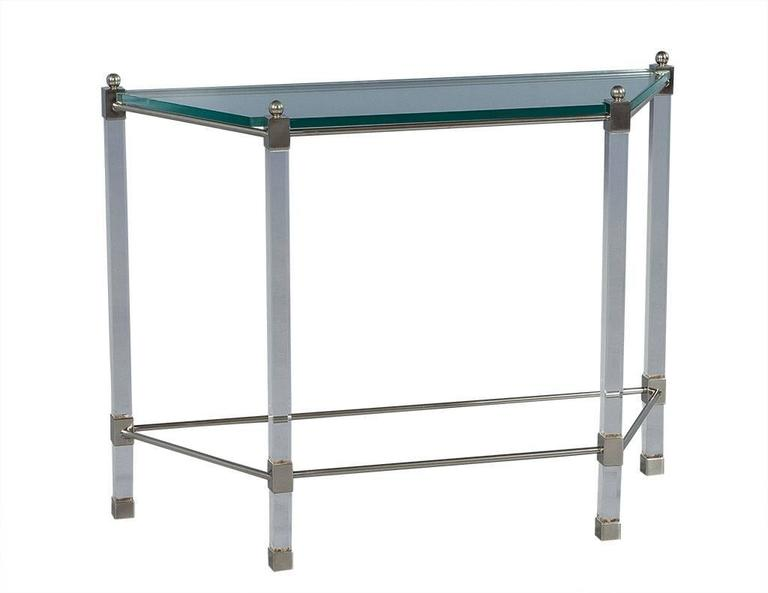 This Mid-Century Modern console sits atop an angular frame with Lucite legs, a tempered glass top and brushed chrome accents and finials on top. Lending to true 1970s French style, this simple and sophisticated piece is a great fit for any living