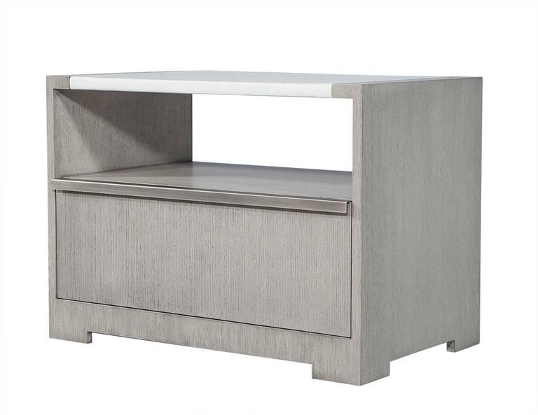 This transitional style pair of night tables is made to order out of rift cut white oak with a vinyl wrapped centre block on top. There is a lower open shelf and below that a drawer and removable back panel in wood to match. Each table is finished