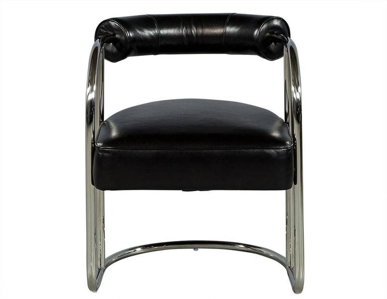 This Bauhaus inspired chair is simple yet luxurious. It is crafted out of a tubular stainless steel frame with a black leather seat and bolster style back cushion enveloping the frame. A cool addition to any modern sitting area!