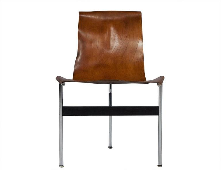 These Mid-Century Modern T-chairs are a picture-perfect combination of rustic texture and modern flair. They are each composed of cognac colored saddle leather slung across a T-shaped tubular steel frame with a T-shaped connector between the three