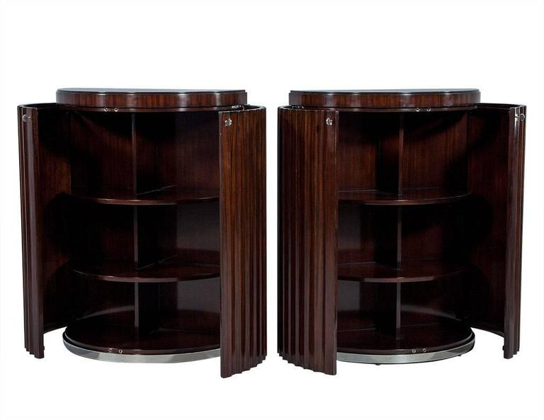 These Art Deco commodes are crafted out of rosewood into a Demilune shape, with louvered double doors with lock and key entry. The interior is divided into two sections, both consisting of three shelves, and the whole piece sits atop a stainless