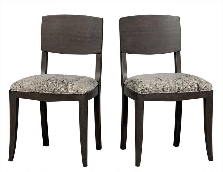 These Art Deco style dining chairs are sleek and stylish. They are crafted out of a show wood frame with a square back and refinished in a grey satin stain. Re-upholstered in textured light grey fabric, this set is gorgeous, perfect for an erudite