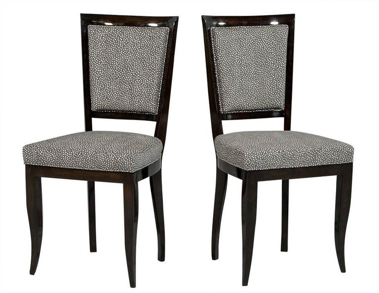 These Art Deco dining chairs are a treat for the eyes! They are fully restored and sit atop the original Art Deco frames with a high, show wood back and sabre legs. They are finished in a high gloss, dark mahogany finish stain, with the inside seat