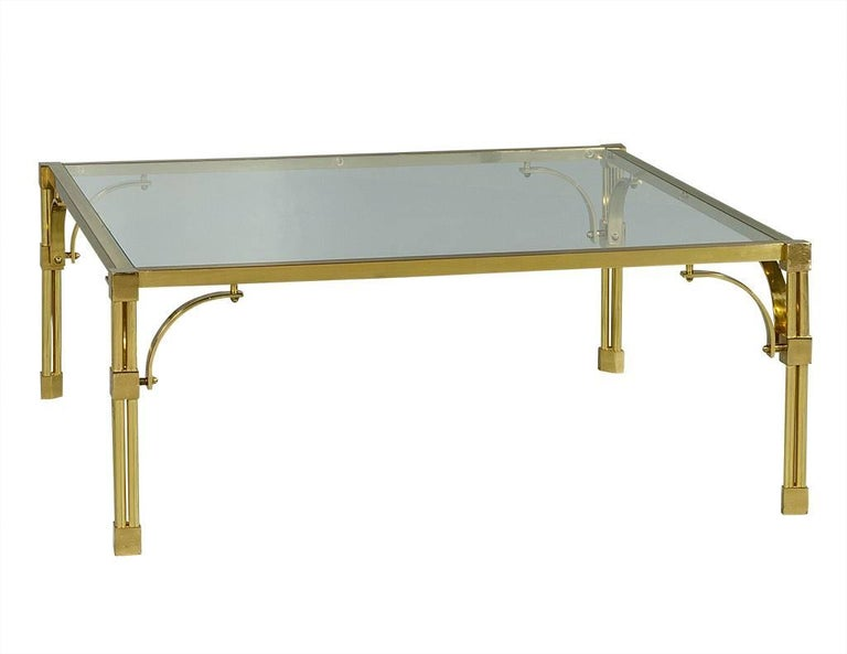This chinoiserie style cocktail table has the perfect amount of detail. The polished brass frame showcases a subtle Asian motif above the tri-column legs, the base of which feature square knuckles. It is topped with a piece of square glass, adding