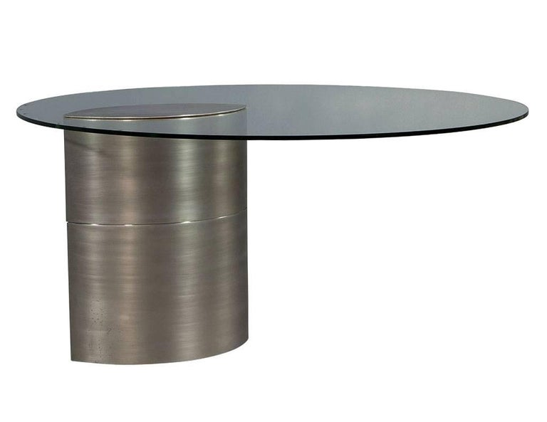 Original 1970s design, featuring thick round glass top with a ellipse shaped brushed chrome base, offset to one side. The extreme weight of the pedestal holds the table secure.  Please note shipping charges are quite expensive due to the sheer