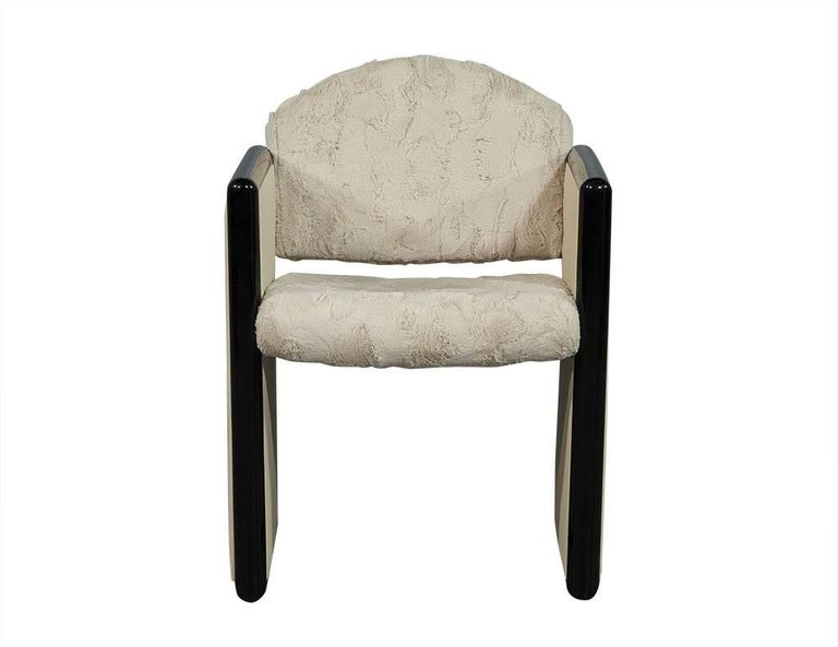 This Modern accent chair is truly one of a kind. Featuring a very soft faux fur seat with square sides in cream leather trimmed with black lacquered wood. The interested mixed media concept makes this chair a unique addition to a daring home!