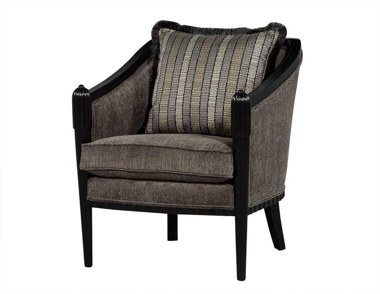 These Art Deco lounge chairs are designed by Baker. Draped in cloth fabric, each chair has black wood on the top edge of the armrests and backrest, with legs in black wood as well. Each chair also has a large backrest pillow with a three color