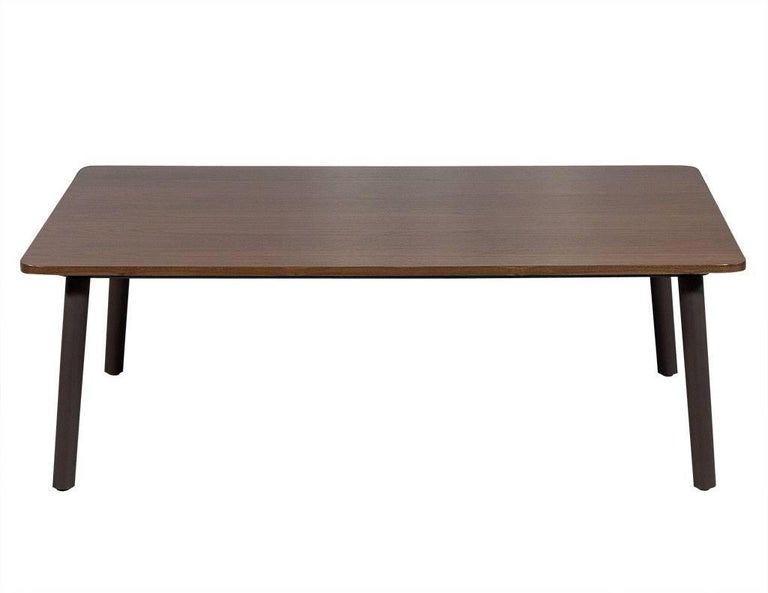 This Mid-Century Modern styled coffee table is custom-made and crafted out of solid walnut with rounded corners. It sits atop angled grey/brown legs with a matte finish. A striking piece perfect for a current living room!