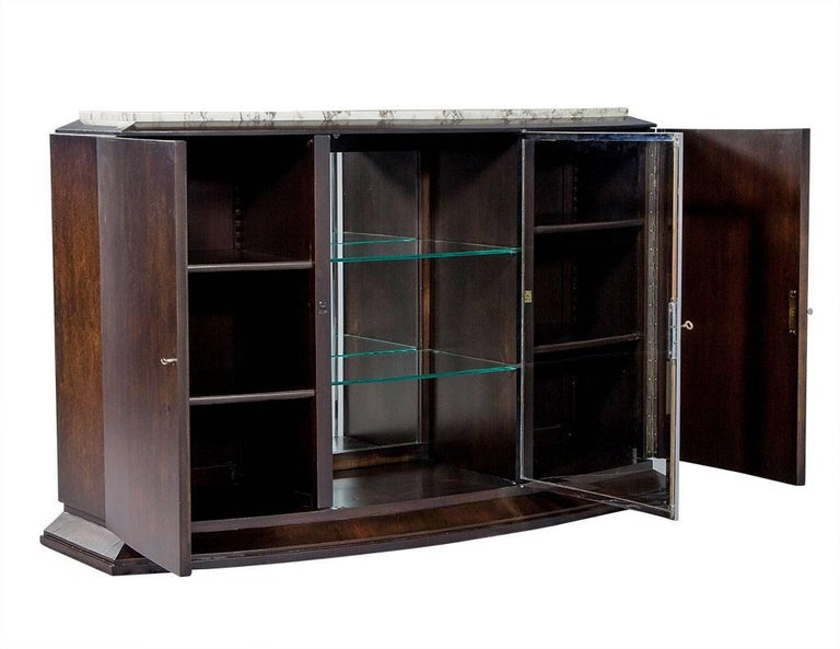 Gorgeous newly restored Art Deco bow front sideboard, enveloped in burled wood veneers. Original marble top with case divided into three lower shelved storage compartments, with the central compartment for display outfitted with glass shelves and a
