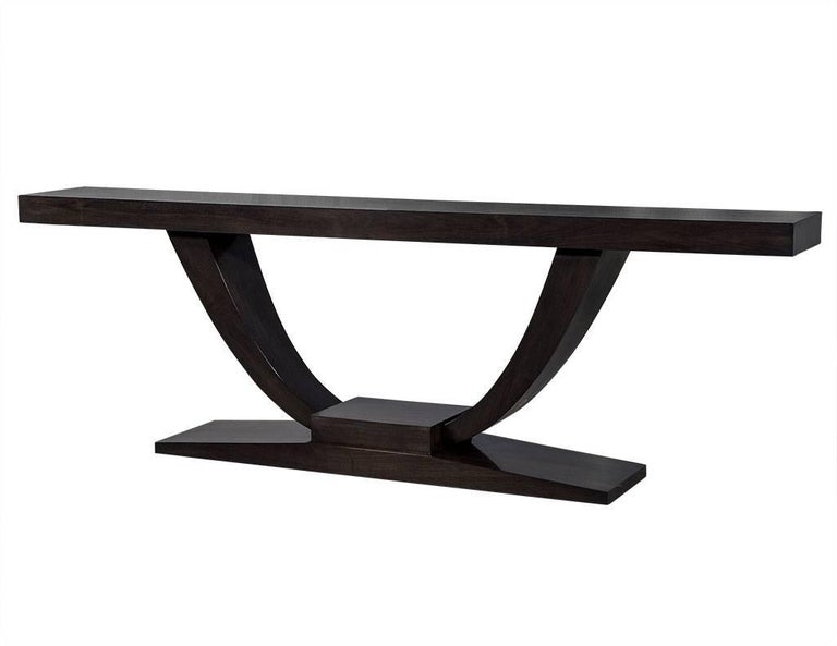 This custom Art Deco walnut console table is absolutely gorgeous. With a large U-shaped base and pedestal, this piece is like a work of sculpture, perfect for behind a sofa or against an entryway wall to really make a statement! Designed and custom