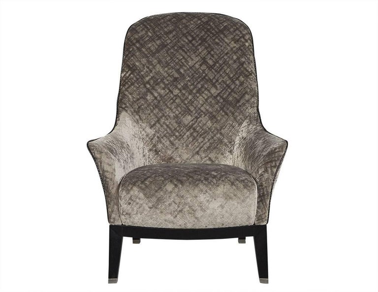 Gorgeous high back lounge chair. This lounge chair is simply luxurious. Curved armrests, braided leather piping on the edges, and a black wood base sitting atop angled legs with silver feet tips. Newly reupholstered, this chair is a true lesson in