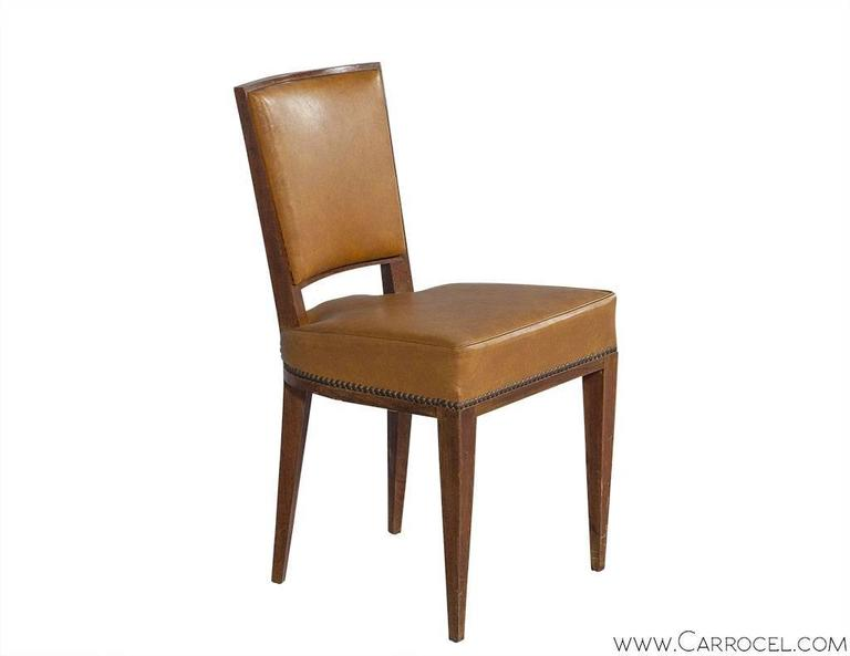 This beautifully constructed set of walnut Art Deco era chairs boasts curved solid walnut frames and beautifully aged, original leather upholstery with head-to-head nails along the base.  With deep a deep rich patina walnut, elegantly tapered legs,