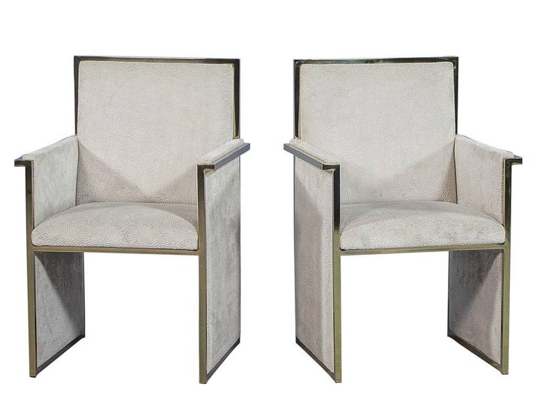 These Mid-Century Modern armchairs are absolutely eye-catching. They are composed of a polished brass frame with floating seating upholstered in a textured pale grey velvet. A perfect fit for a neutral yet daring dining room! Part of the Revival
