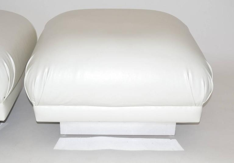 Pair of oversized ottomans or poufs in the soufflé style. Features large square cushions with pleated corners over a chrome banded wood base. Upholstered in white leatherette vinyl, 1970s.