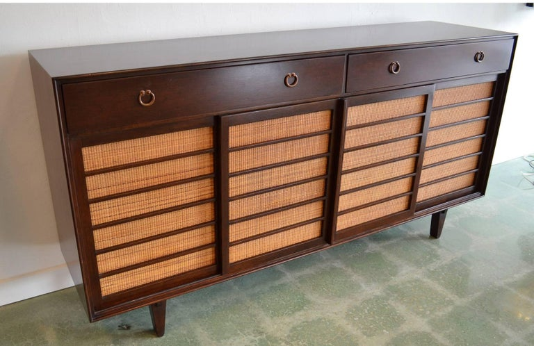 Sideboard credenza for Dunbar designed by Edward Wormley Mid-Century Modern grass front 671-A. Japanese-inspired in walnut with grass-covered sliding doors opening to pull-out and partitioned drawers with bronze pulls on exposed joinery legs.