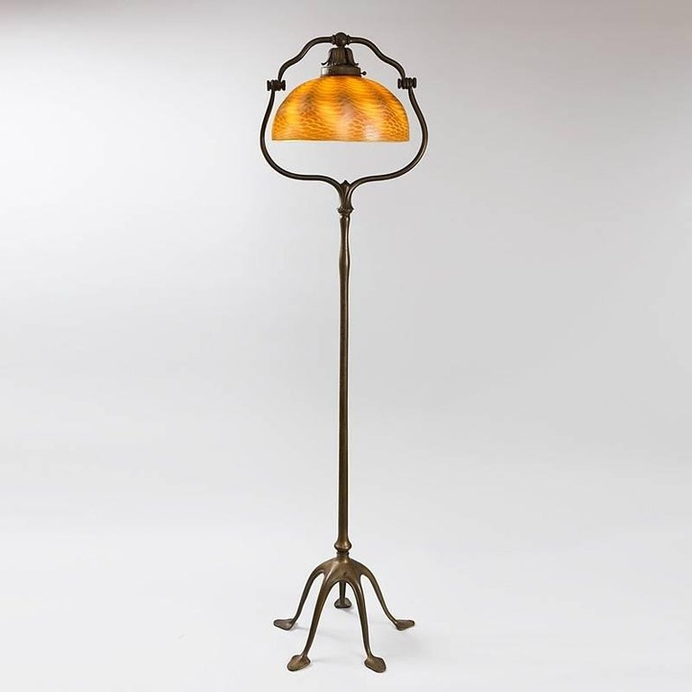 "A Tiffany Studios New York Favrile glass and patinated bronze floor lamp with a golden ""Damascene"" shade with iridescent decoration suspended within a five-footed ""Harp"" base, circa 1900.