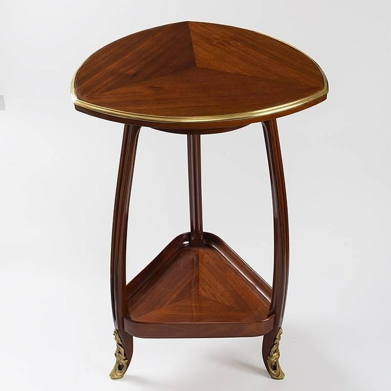 A triangluar French Art Nouveau table by Louis Majorelle. This two-tiered triangular table is made of mahogany. Its carved legs are finished with gilt bronze sabots, circa 1910.  A similar table is pictured in: The Paris Salons 1895-1915, Vol. III: