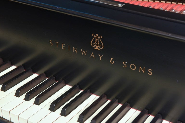 Steinway grand piano from 1921, completely rebuilt to original specifications and re-finished by Steinway, New York in a mat black finish. Complete with a concert bench with black tufted leather seat matching the piano. Model S.