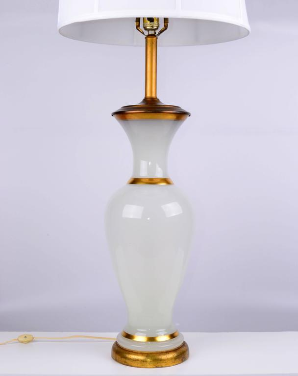 1950s opal glass and brass table lamp on a wood base with gilt finish. Harp and finial included. Wired for the U.S. and has a three-way function; uses a 50-100-150W bulb. Height to top of socket: 30.75