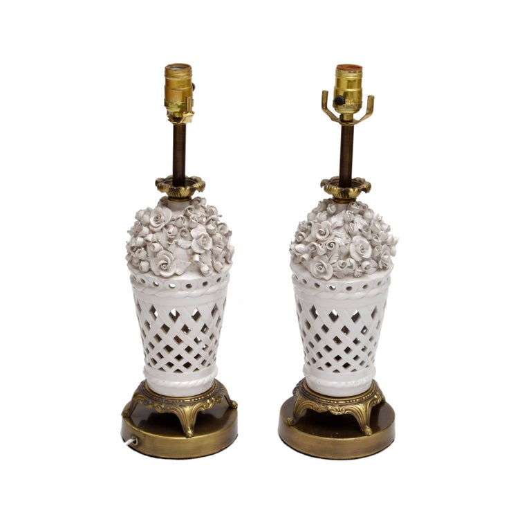 A pair of white porcelain table lamps in capodimonte style with bronze feet and ruffle. In perfect working condition and each uses a max. 60 watts light bulb.