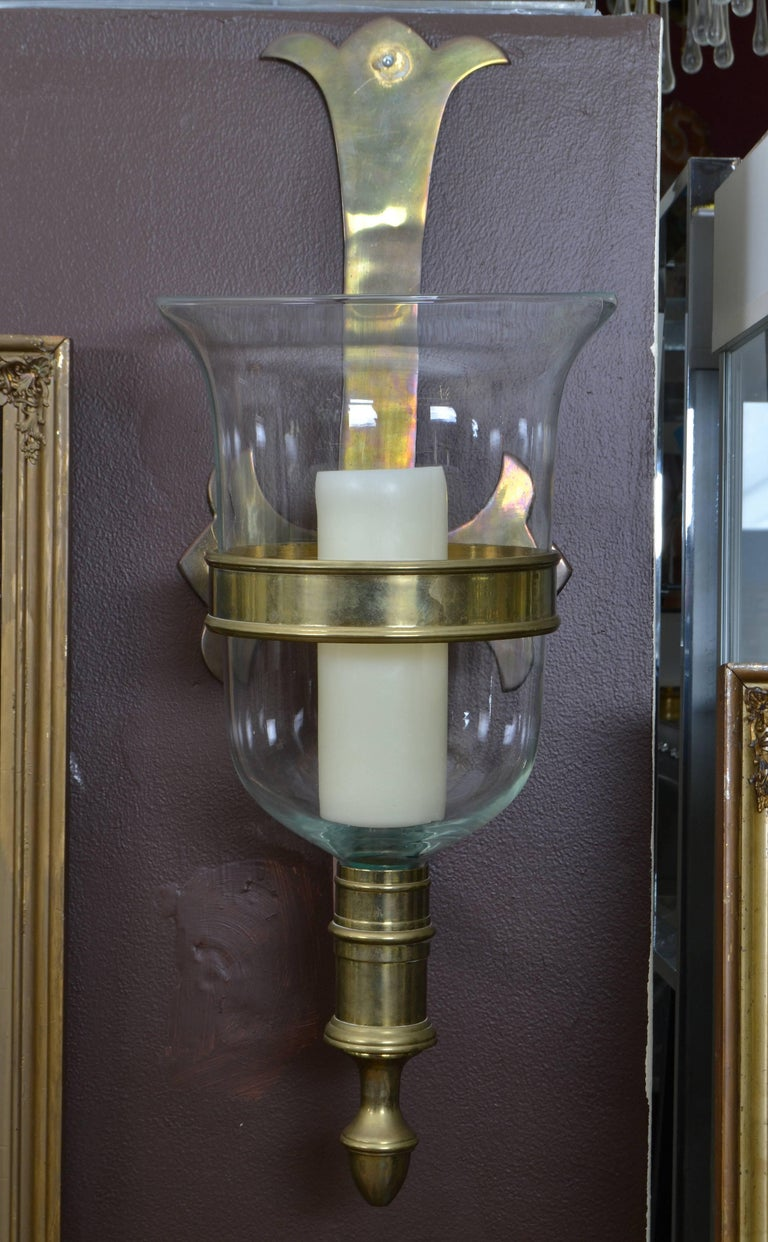 A pair of glass bell hurricane lamps with bronze brackets.