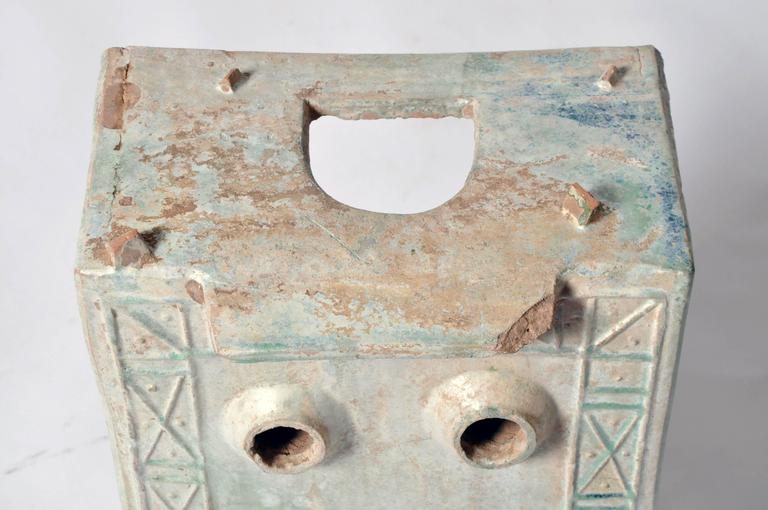 This squat, rectangular piece of tomb pottery features an arched door below a trapezoidal pediment, three circular openings on its top and an incised, decorative border in a geometric pattern. Its light green glaze has developed a handsome