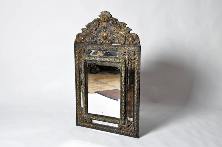 Brass frame with arched top and repousse decoration, rectangular beveled mirror plate. Exceptionally fine brass repousse supplemented with another metal, possibly copper. The quality of decoration makes earlier than 19th century date plausible.