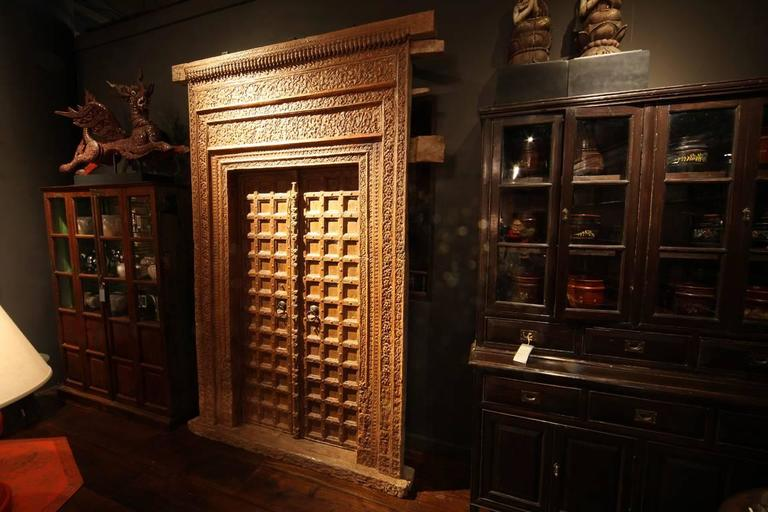 This monumental carved Indian entrance door is made from Chechum wood and features an impressive and intricate door frame.